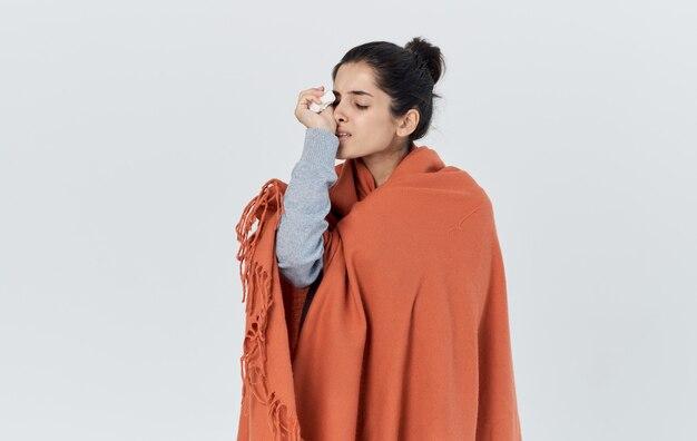 Portret van een mooie vrouw met een oranje plaid op haar schouders gezondheidsproblemen allergie servet