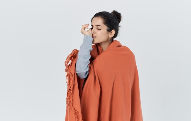 Portret van een mooie vrouw met een oranje plaid op haar schouders gezondheidsproblemen allergie servet.
