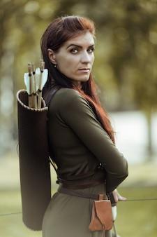 Portret van een mooie vrouw met een oude pijlkoker met pijlen op haar rug
