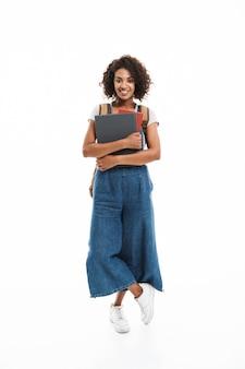 Portret van een mooie vrouw met een rugzak die lacht en oefenboeken vasthoudt die over een witte muur worden geïsoleerd