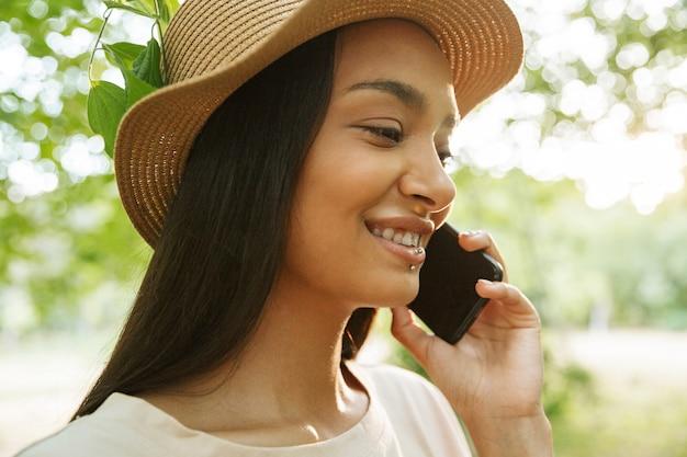 Portret van een mooie vrouw met een strohoed en lippiercing die op een smartphone in een groen park praat
