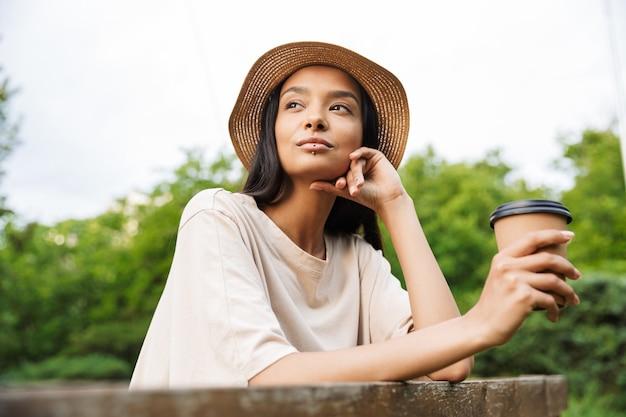 Portret van een mooie vrouw met een strohoed en lippiercing met een papieren bekertje met afhaalkoffie in een groen park
