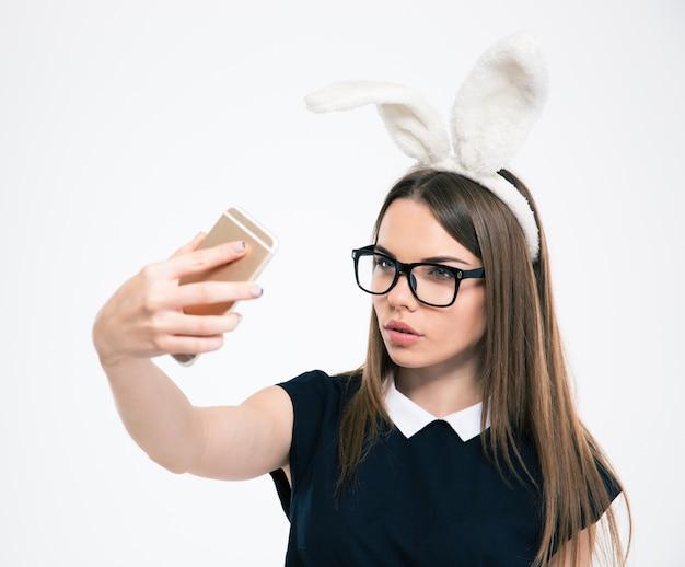 Portret van een mooie vrouw met konijnenoren die selfie-foto maken op smartphone geïsoleerd
