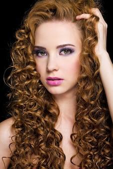 Portret van een mooie vrouw met lang krullend haar - op een zwarte achtergrond