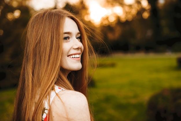 Portret van een mooie vrouw met lang rood haar en sproeten wegkijken lachend tegen zonsondergang buiten.