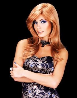 Portret van een mooie vrouw met lange rode haren en de blauwe make-up van het manieroog - op zwarte muur