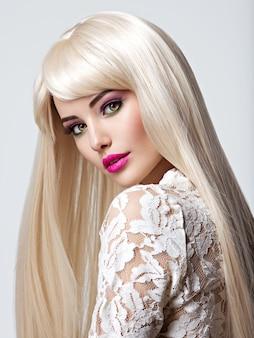 Portret van een mooie vrouw met lange witte rechte haren en lichte make-up. gezicht van een mannequin met roze lippenstift. mooi meisje poseren.