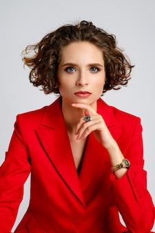 Portret van een mooie vrouw met natuurlijke make-up, kort krullend haar en een rode jas die de kin ondersteunt