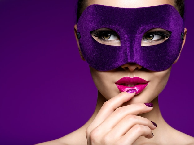 Portret van een mooie vrouw met paarse nagels en violet theatermasker op gezicht.