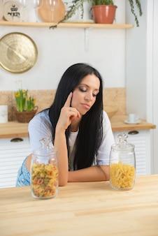 Portret van een mooie vrouw met pasta in de keuken kiest welke te koken
