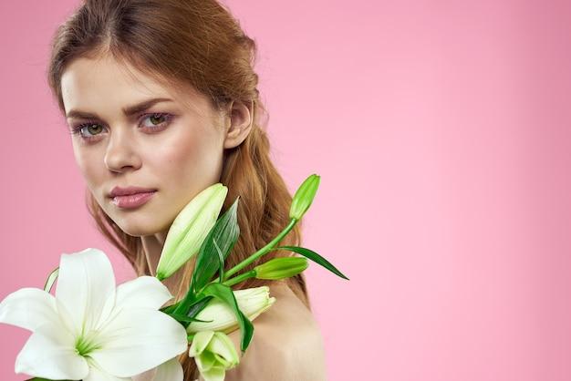 Portret van een mooie vrouw met witte bloemen in haar handen op roze