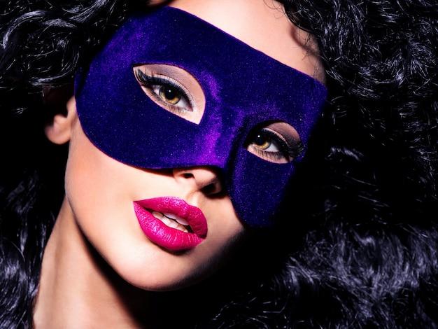 Portret van een mooie vrouw met zwarte haren en blauw theatermasker op gezicht.