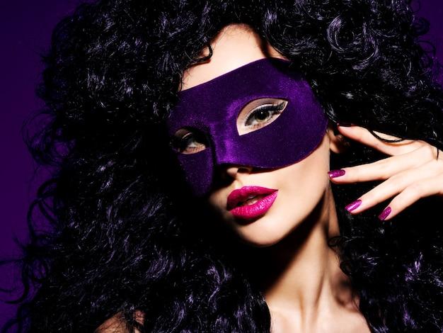 Portret van een mooie vrouw met zwarte haren en violet theatermasker op gezicht.