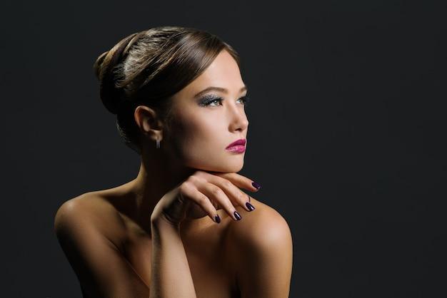 Portret van een mooie vrouw op een donkere achtergrond