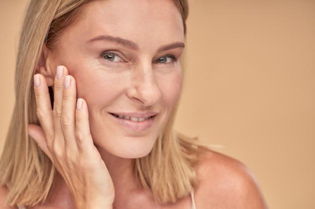 Portret van een mooie vrouw van middelbare leeftijd die haar schone huid aanraakt en naar de camera glimlacht terwijl