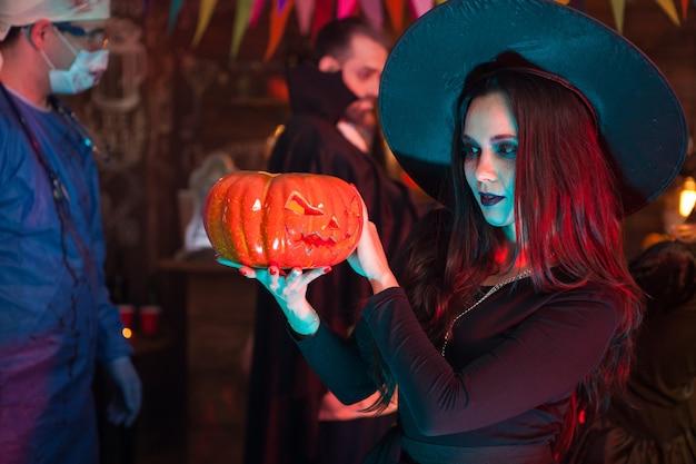 Portret van een mooie vrouw verkleed als een heks die donkere magie doet op een pompoen voor halloween. dracula op halloween-feest.