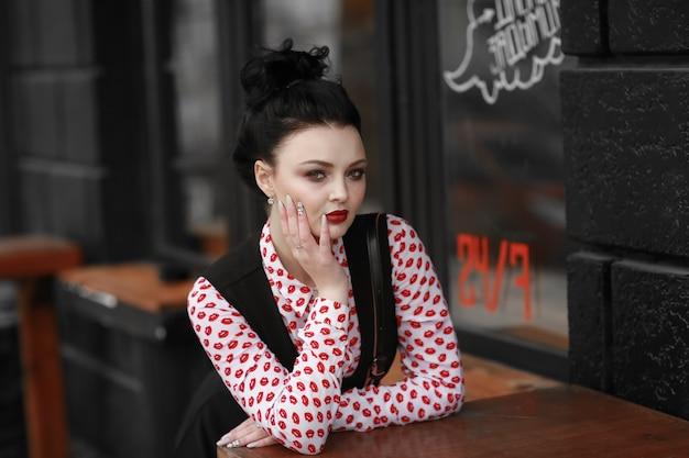 Portret van een mooie vrouw zitten aan een tafel in een straat café