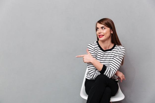 Portret van een mooie vrouw zittend op een stoel