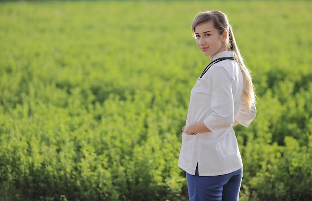 Portret van een mooie vrouwelijke arts of verpleegster op groene grasachtergrond