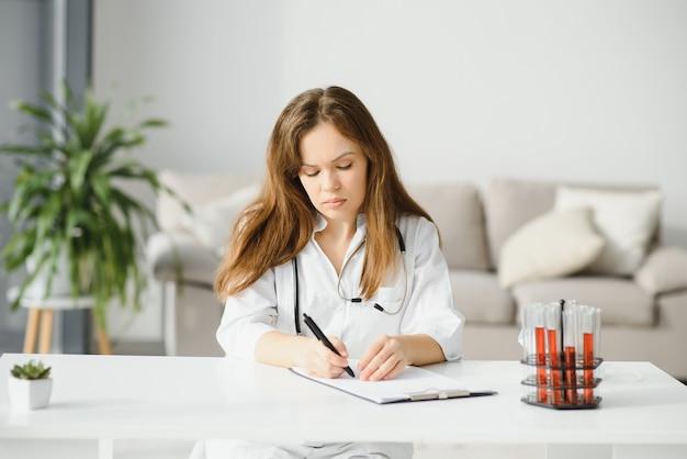 Portret van een mooie vrouwelijke scheikundige op zoek naar het analyseren van een bloed reageerbuis in een laboratorium
