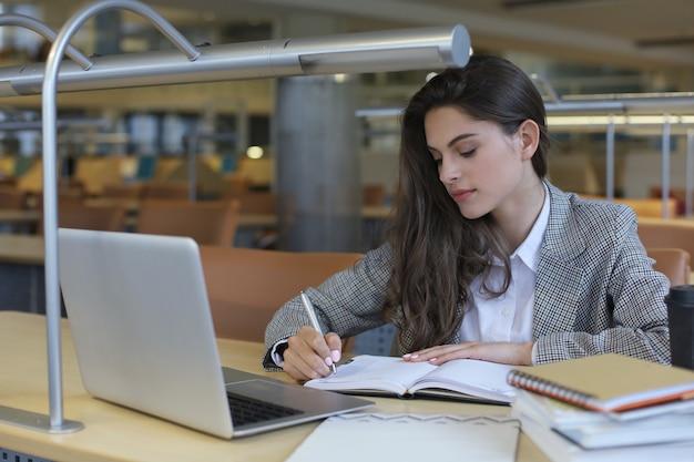 Portret van een mooie vrouwelijke student met laptop in bibliotheek.