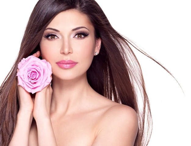 Portret van een mooie witte mooie vrouw met lang steil haar en roze roos in het gezicht.