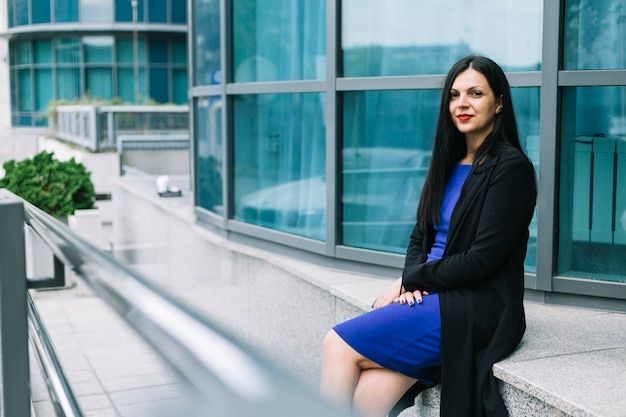Portret van een mooie zakenvrouw zitten buiten kantoorgebouw