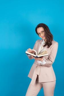 Portret van een mooie zelfverzekerde zakelijke studente met een bril en een licht pak met een boek in het midden isoleer op een blauwe achtergrond