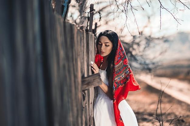 Portret van een mooie zwarte haired meisje in een vintage jurk staande in de buurt van houten hek. jonge vrouw model poseren in een russische nationale stijl. rode sjaal