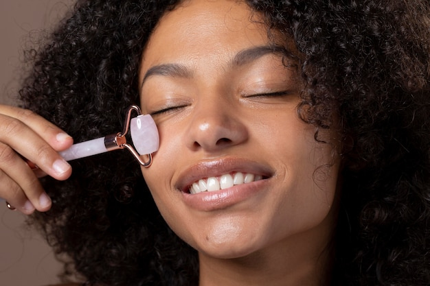 Portret van een mooie zwarte vrouw die een jaderoller op haar gezicht gebruikt