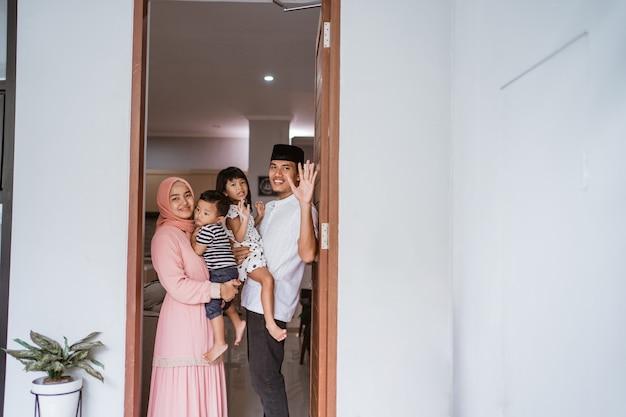 Portret van een moslimfamilie die zich voor hun gastvrije gast thuis tijdens eid mubarak-viering bevindt