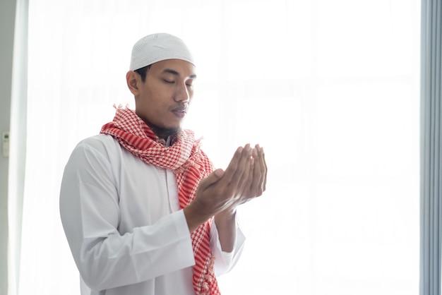 Portret van een moslimman die de hand gebruikt om tegen een wit raam te bidden