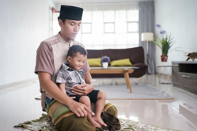 Portret van een moslimvader die thuis bidt terwijl op zijn zoon babysitten
