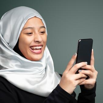 Portret van een moslimvrouw die een mobiele telefoon gebruikt