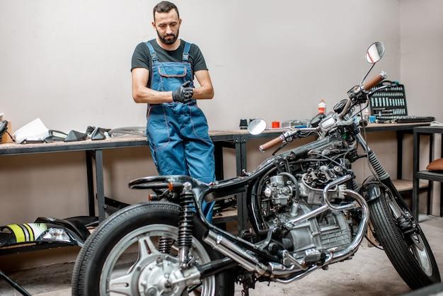 Portret van een motorrijder in een werkende overall die bij de motorfietsen staat tijdens de reparatie in de werkplaats