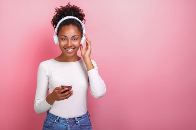 Portret van een mulatmeisje in oortelefoons en een mobiele telefoon houden die bekijkend de camera