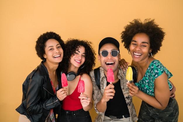 Portret van een multi-etnische groep vrienden die plezier hebben en genieten van de zomer terwijl ze ijs eten tegen gele achtergrond.