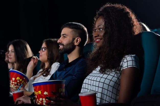 Portret van een multiculturele groep vrienden genieten van films samen in de bioscoop