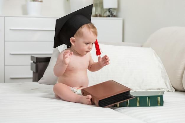 Portret van een naakte babyjongen met een zwarte afstudeerpet die naar een stapel boeken kijkt