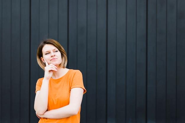 Portret van een nadenkende jonge vrouw die weg kijkt