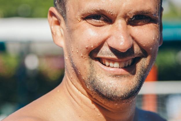 Portret van een natte man. druppels druppelen over mijn gezicht. gelukkig man na hard lichamelijk werk. krachtoefeningen, gewichtsverlies, bruinen, zwemmen