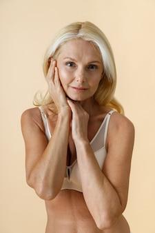 Portret van een natuurlijke rijpe vrouw met blond haar in wit ondergoed die naar de camera kijkt en haar aanraakt