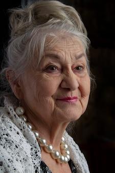 Portret van een negentigjarige vrouw. mooie oude dame. luxe grootmoeder op een zwarte achtergrond. oudere schoonheid. de grijsharige, goed verzorgde gepensioneerde.