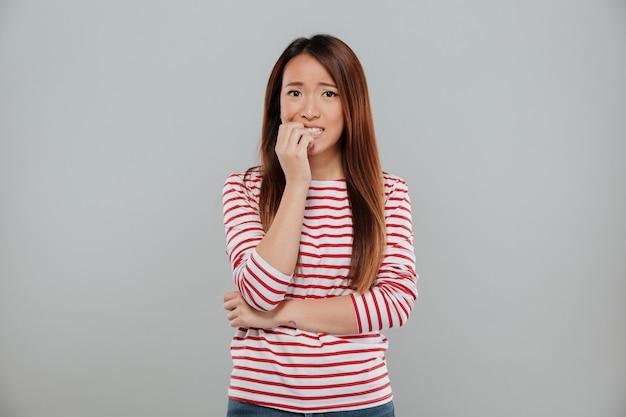 Portret van een nerveus aziatisch meisje dat haar spijkers bijt