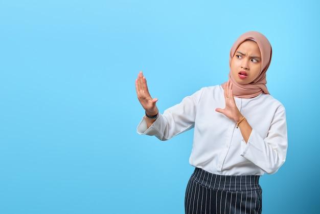 Portret van een nerveuze, angstige jonge aziatische vrouw die een stop maakt, geen gebaar over een blauwe achtergrond beweegt