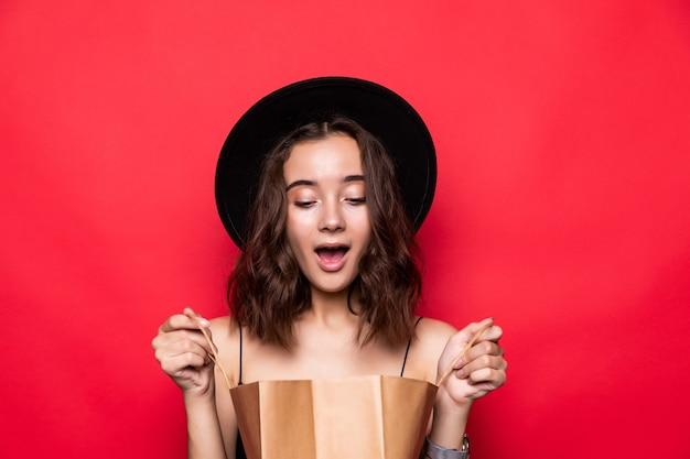 Portret van een nieuwsgierige jonge vrouw die in zomerhoed in boodschappentassen kijkt die over rode muur wordt geïsoleerd