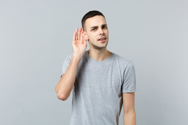 Portret van een nieuwsgierige jongeman in vrijetijdskleding die hand in de buurt van oor hoort