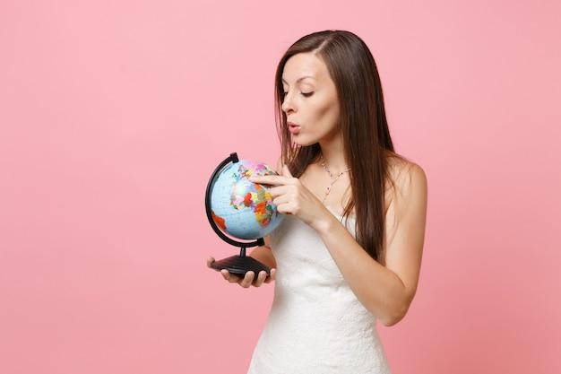 Portret van een nieuwsgierige vrouw in witte kanten jurk die met de wijsvinger op de wereldbol wijst en plaats kiest choosing