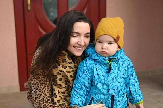 Portret van een nors kind en een vrolijke moeder. humeurig kind op straat.
