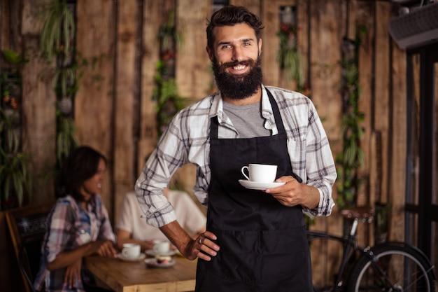 Portret van een ober met een kopje koffie